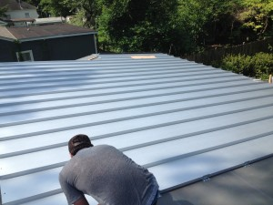 Roofer installing metal roof on home in hampstead nc