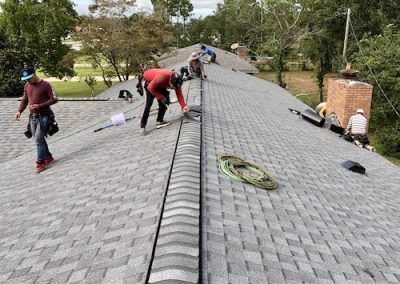 workers installing ridge cap on shingle roof in leland nc